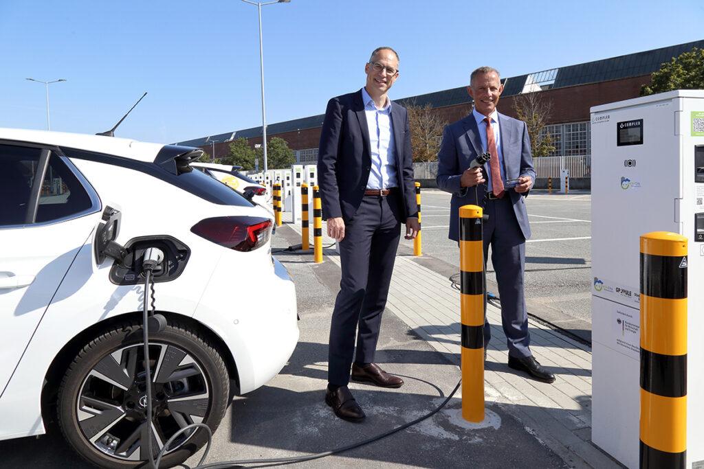 Oberbürgermeister Udo Bausch (li) und Ralph Wangemann, Arbeitsdirektor der Opel Automobile GmbH, nehmen die erste Rüsselsheimer Ladefarm mit 152 Ladepunkten in Betrieb (Foto: Stadt Rüsselsheim am Main / Frank Möllenberg)